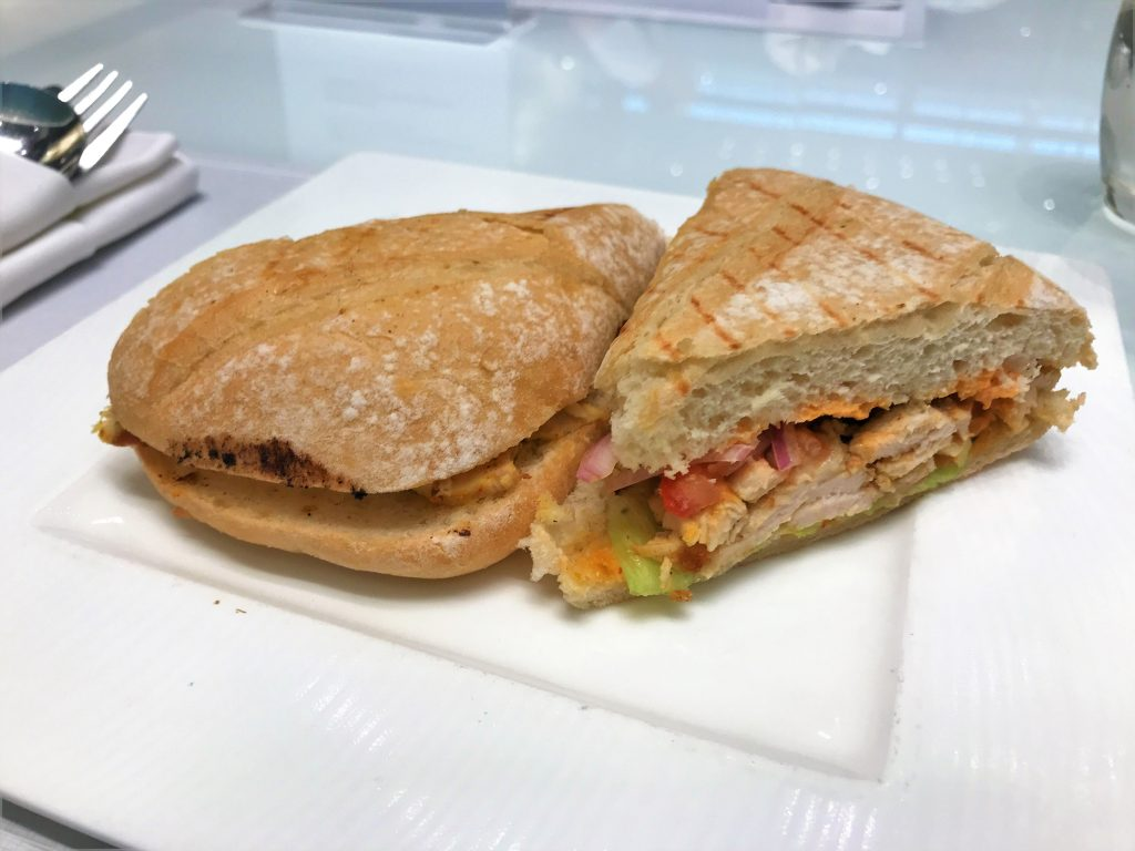 Qatar Airways Business Class Al Mourjan lounge Doha review chicken sandwich deli