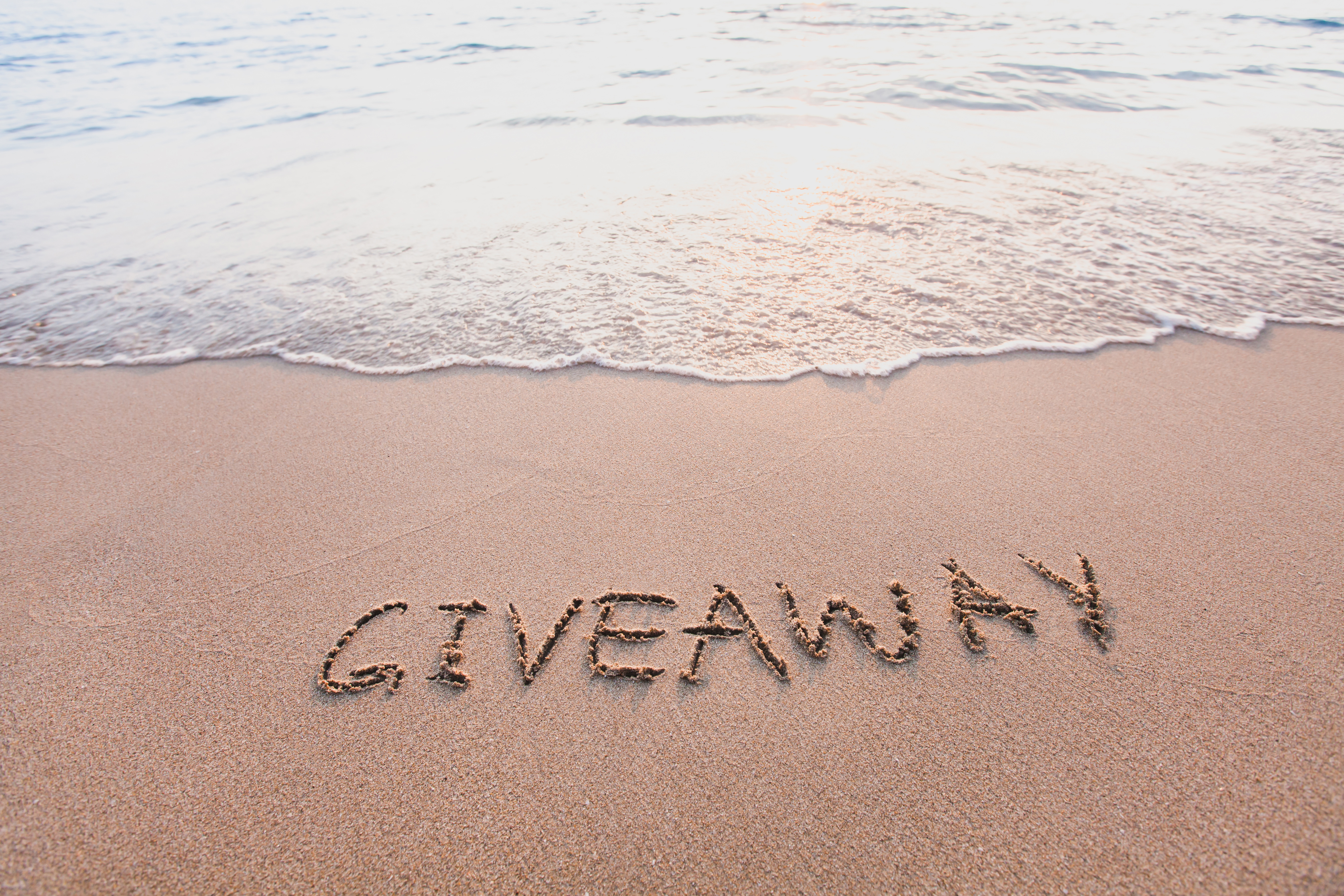 giveaway concept, word message written on the sand